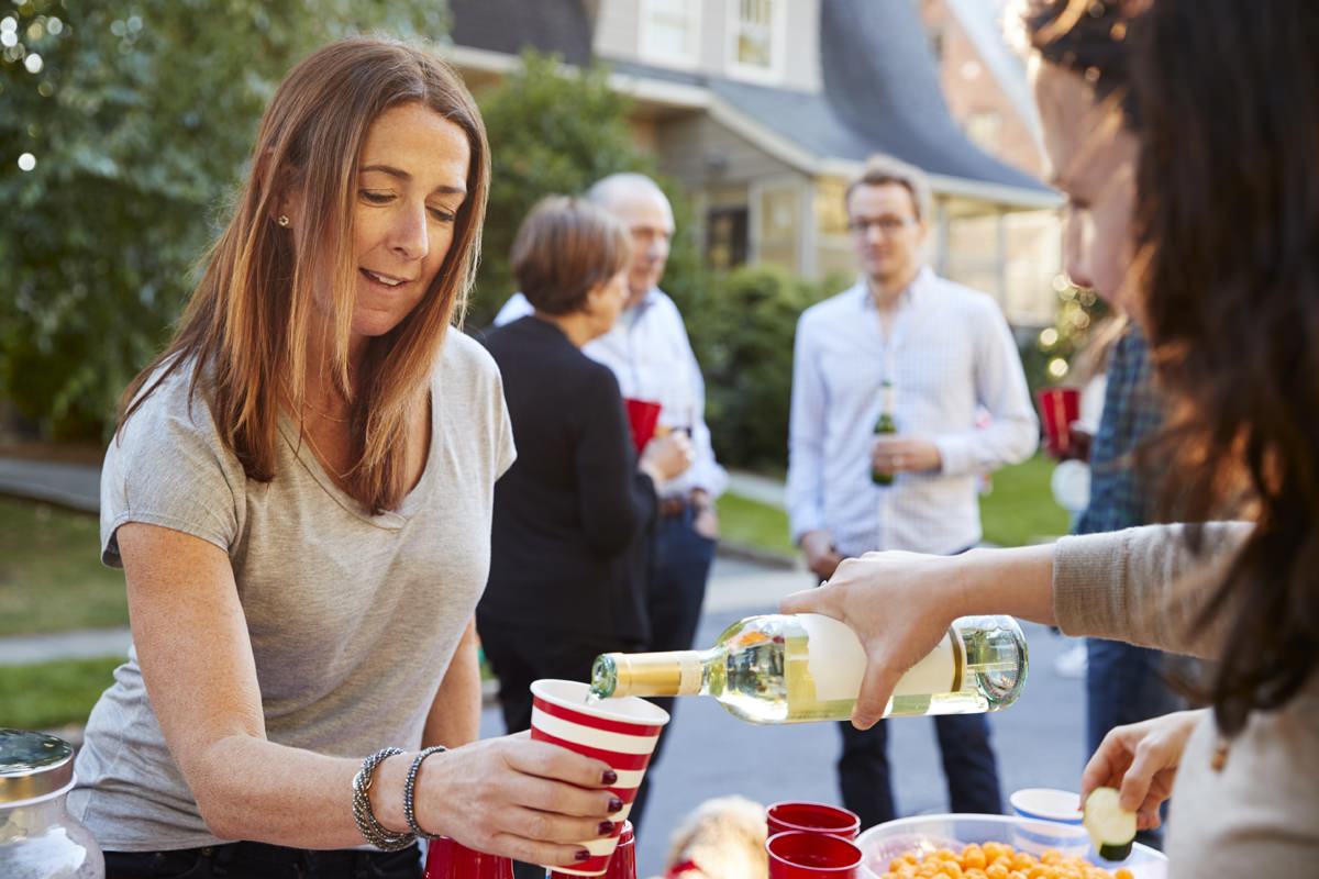 Neighbour pouring a woman a cup of wine at a block party