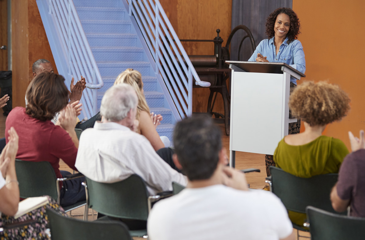 Woman At Podium Chairing Neighborhood Meeting In Community Centre
