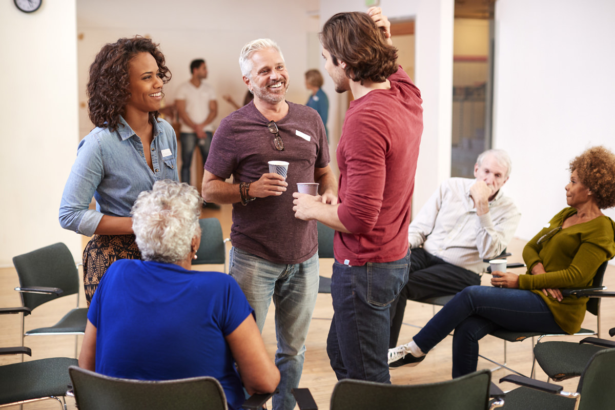 Group Of People Socializing After Meeting In Community Center